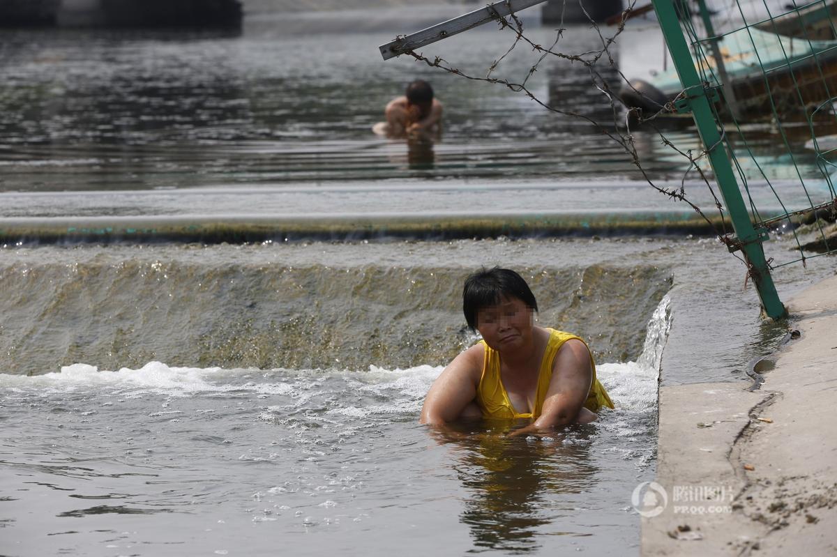 郑州38度高温 大妈水渠消暑完全无视身后裸男