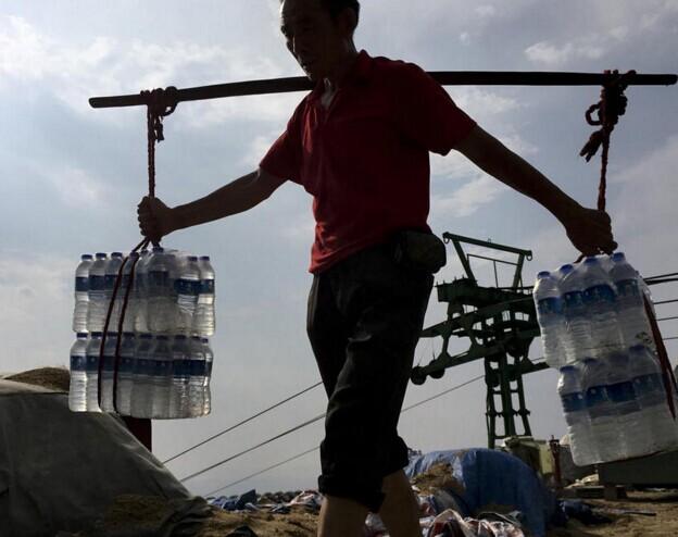 众生相:挑山工每天挑水千斤 一瓶赚一毛