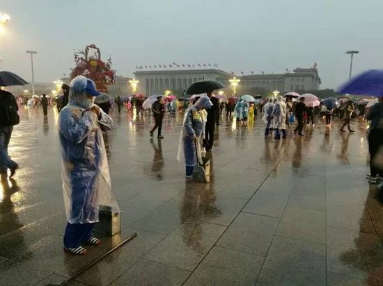 让人感动!天安门广场游客自发为环卫工打伞