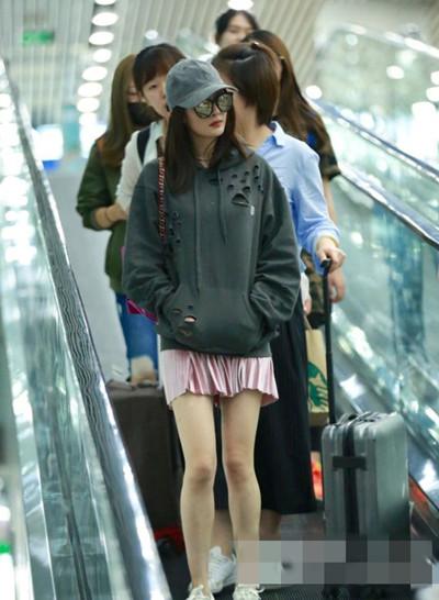 杨幂机场街拍造型示范 粉红百褶短裙美腿尽现