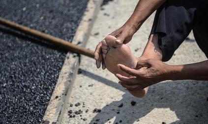 图为张宝印踩着高温沥青施工,脚底仍烫出了血泡。