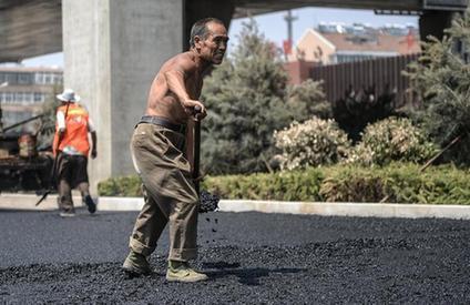 沥青工人赤膊工作。