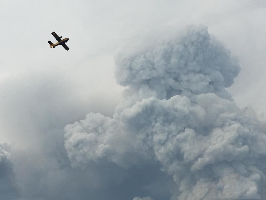图为消防飞机从大火上空飞过。葡萄牙总理科斯塔表示,邻国西班牙18日派出两架飞机向火场投掷水弹。