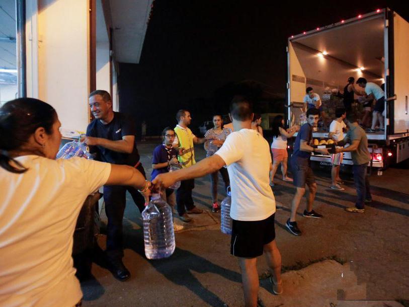 志愿者们帮忙将救援物资从卡车上搬运到临时安置点。火灾目前已造成至少62人死亡,还有数十人受伤,最终死亡人数可能会接近100,两名消防员仍然失踪。葡萄牙当局出动超过700名消防员灌救,但火势未受控。