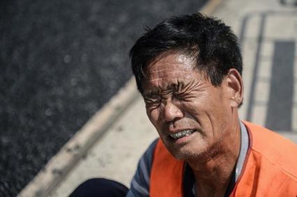 今年 63岁的张宝印从事沥青施工多年,脚上穿着防护鞋,但踩着高温沥青施工,脚底仍烫出了血泡,无奈下只能坐在路边,将血泡刺破再进行施工作业。