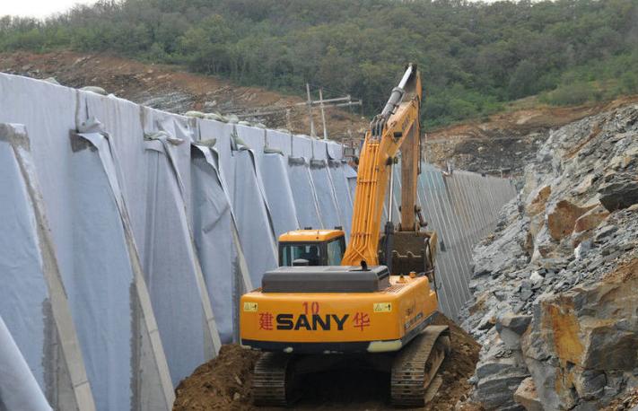 """该项目已列入省市重点建设项目,2016年被中国发改委列为《推进东北地区等老工业基地振兴三年滚动实施方案》127项重大项目之一。图为车辆在对""""地下工厂""""外围进行土石方填埋。"""