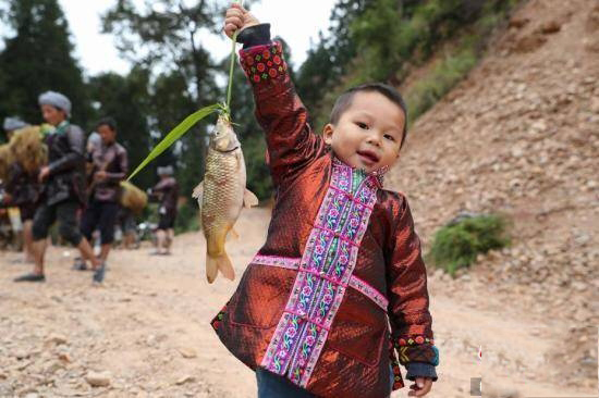 岑秋苗寨一位小朋友手举稻花鱼,准备参加烧鱼盛会。