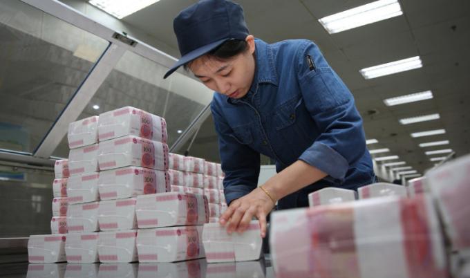 在对自动裁切包装后的人民币进行检测,使用工具将每个分百条对齐,使其误差不超过3毫米。每包产品为10万元。