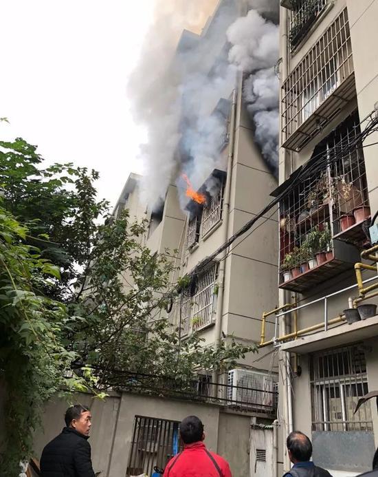 浙江一居民楼发生火灾 保安一边灭火一边搭起梯子救人