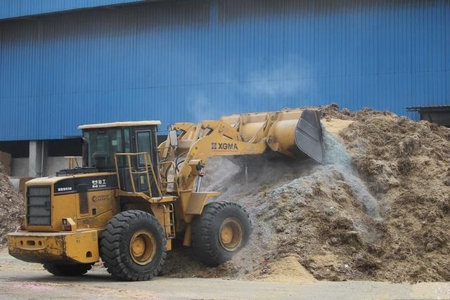 工人使用推土机将残钞废料混合后与废料按照比例参配以保证燃烧的效率和安全。