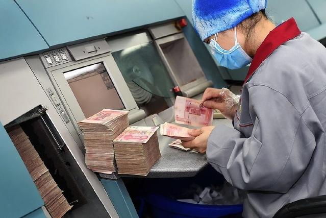 钞票处理中心复点中心工人在识别假币。