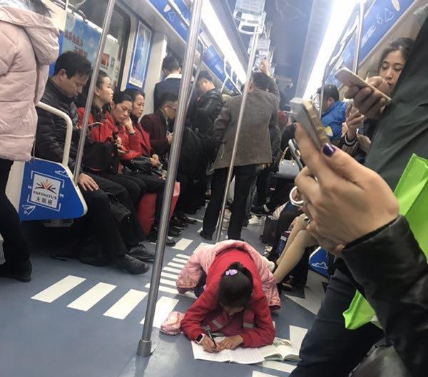 女孩趴地铁上写作业 嘈杂的环境却丝毫不受打扰