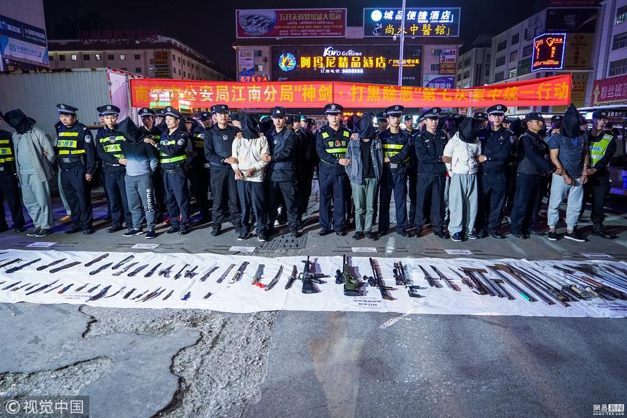 """""""黑社会""""被抓街头示众 地上摆满枪支刀具"""