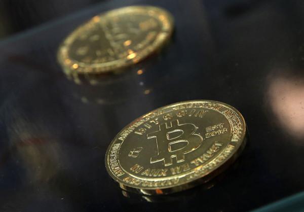 在香港的比特币ATM机旁展示了硬币。