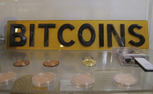 在香港的比特币ATM机旁展示了照片、硬币和标志。