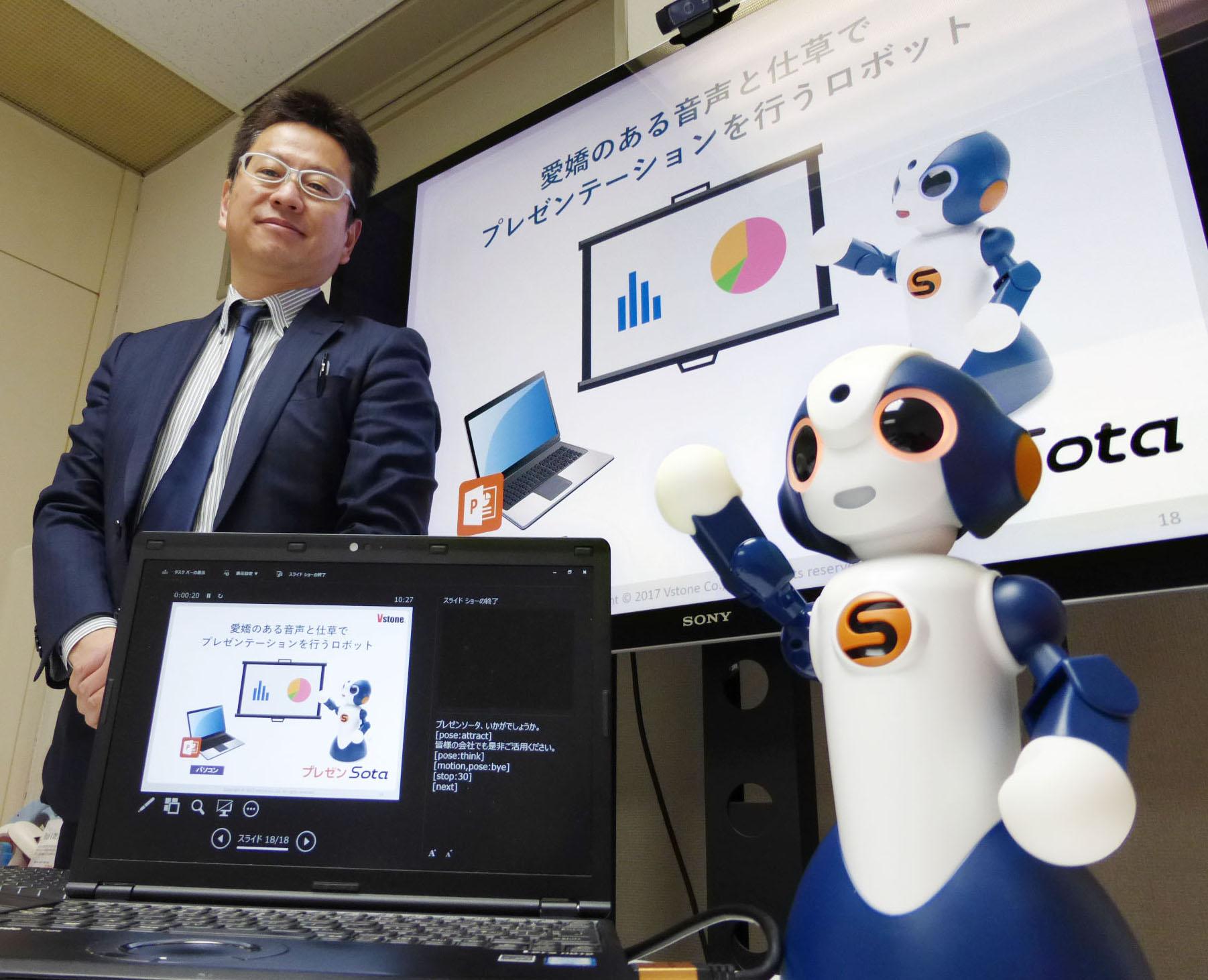 """2017年3月16日,日本制造商Vstone公司开发出了能为人类""""代理""""做陈述报告的机器人""""Presentation Sota""""。左侧为该公司社长大和信夫。"""