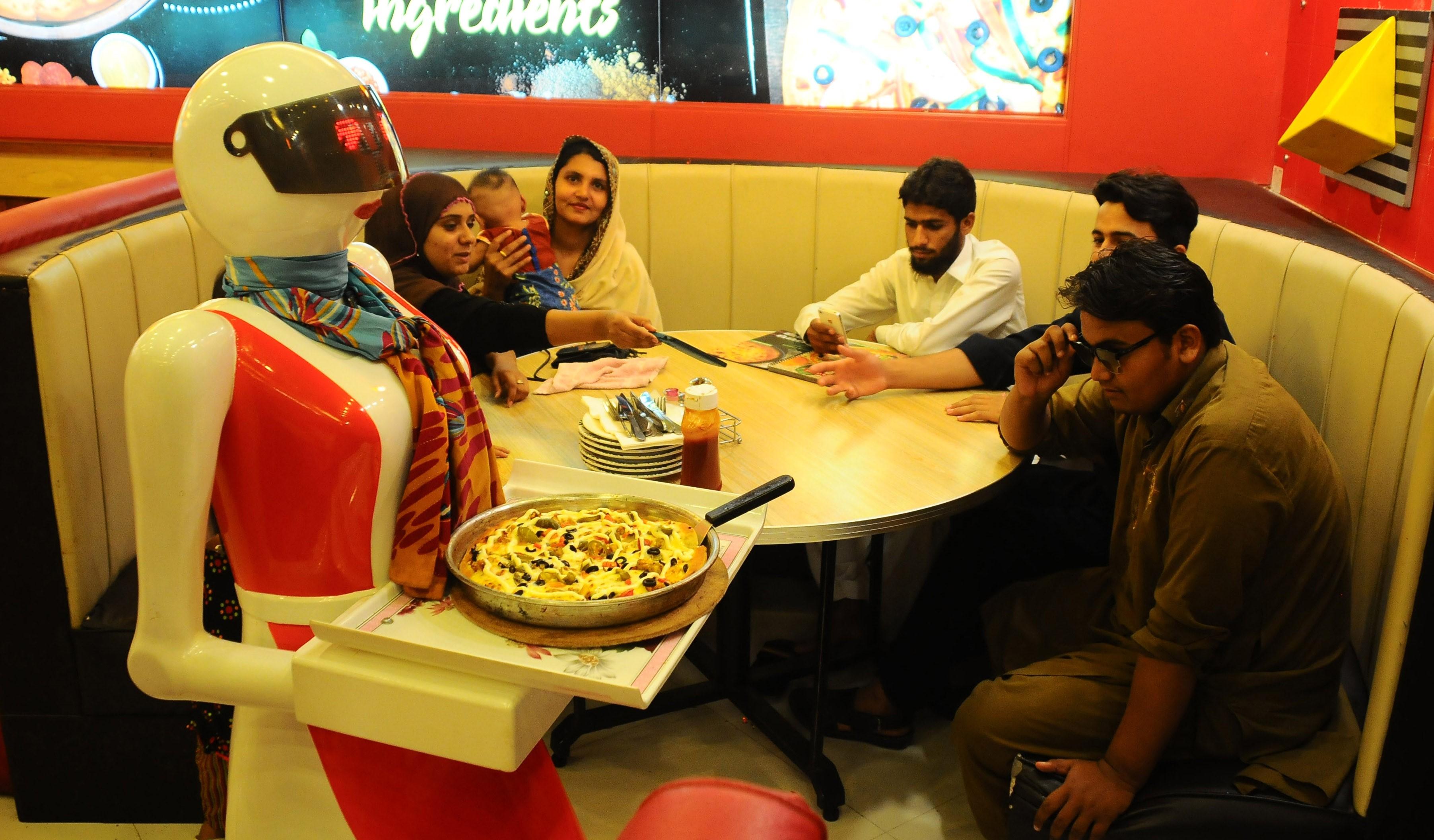 2017年7月8日,巴基斯坦木尔坦,在当地一家披萨店内,机器人充当服务员为客人服务。这些机器人都是由披萨店老板的儿子Osama Aziz所研发的,Osama Aziz是一名电气工程师。