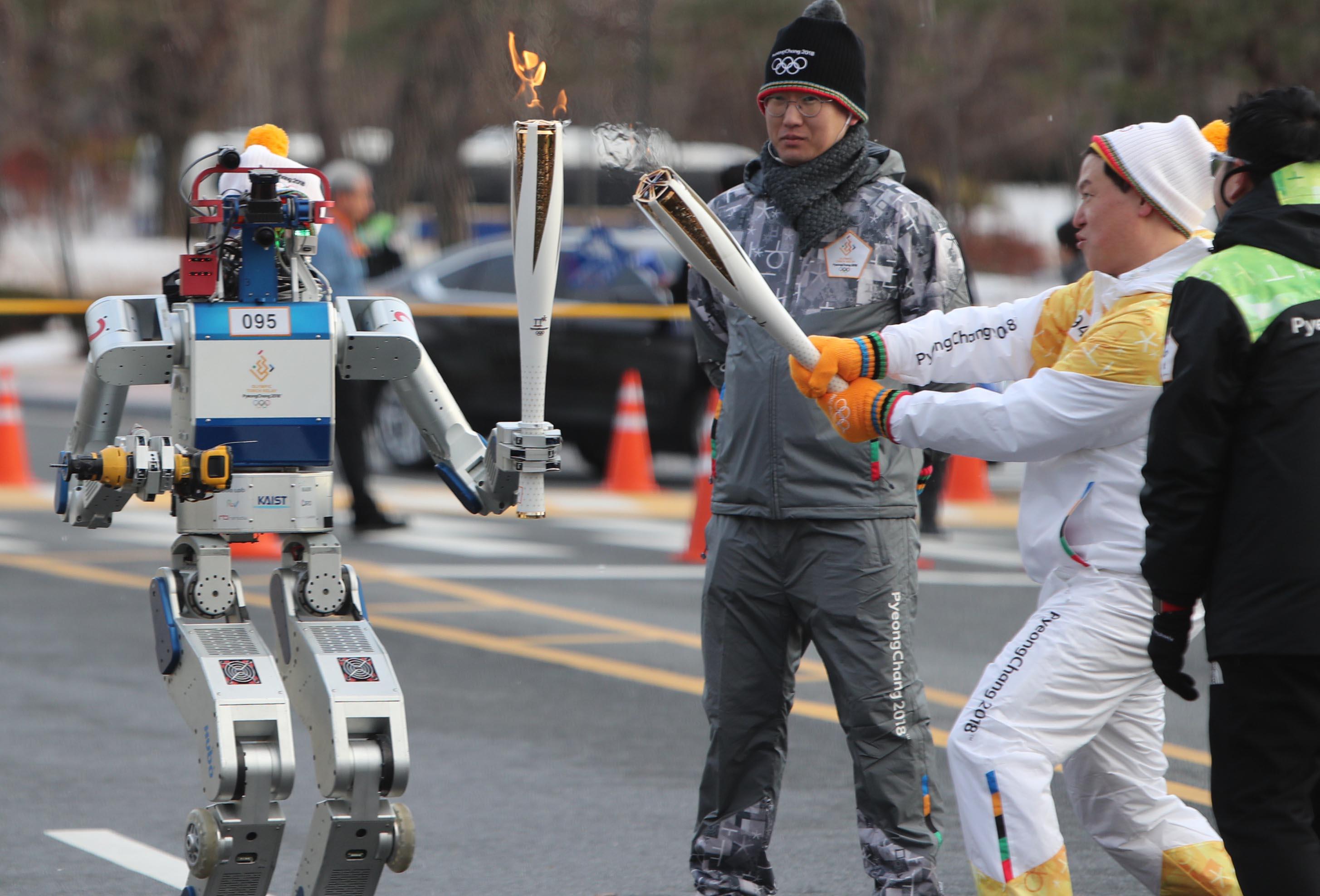 当地时间2017年12月11日,韩国大田,2018平昌冬奥会火炬传递,韩国科学技术学院研发的一款人形机器人HUBO成为一名火炬手,创造机器人传递圣火的首个世界纪录。