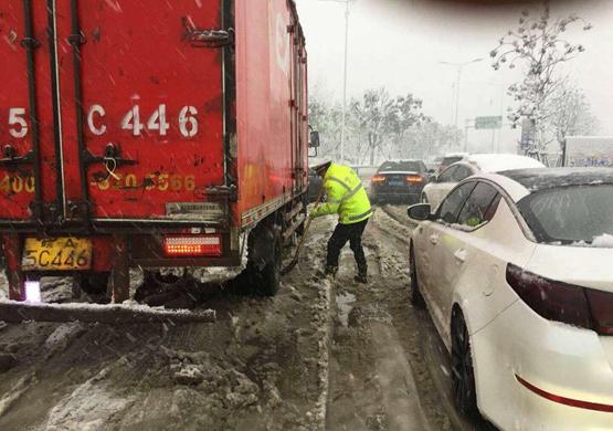 合肥交警在清理路面积雪,保障道路通行。