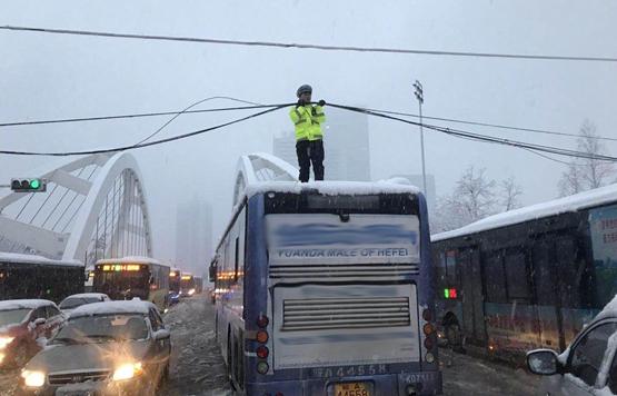 交警果断找来一辆公交车,用身体当线杆,托起坠落的电缆。
