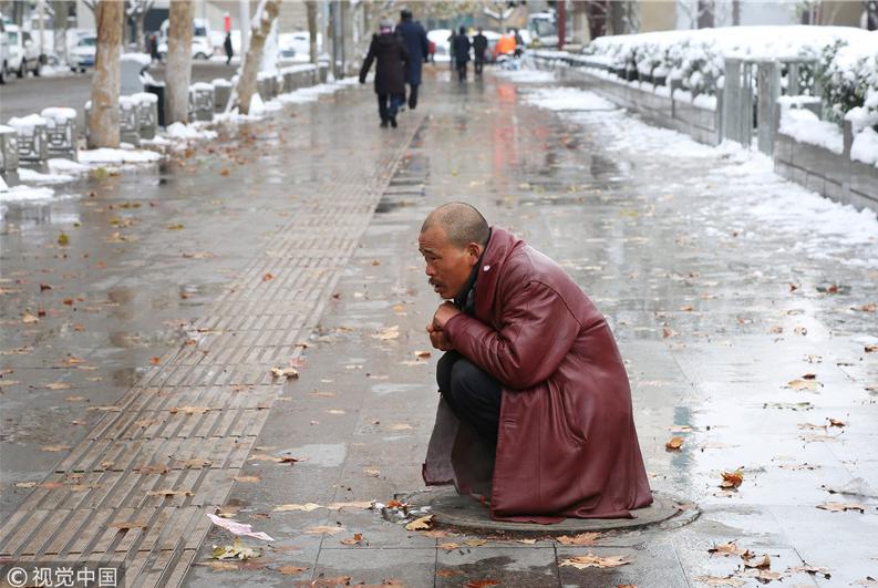 据一名身穿酒红色上衣的男子介绍,他是周边建筑队的民工,由于下雪后工地停工,他为了取暖,便找到了一处紧邻暖气管道、冒有热气的窨井盖。这名男子衣服上有好个几个破洞,大雪中,他在窨井盖上足足蹲了3个多小时。