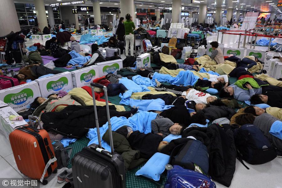 韩机场航班因降雪延误 乘客露宿机场席地而睡