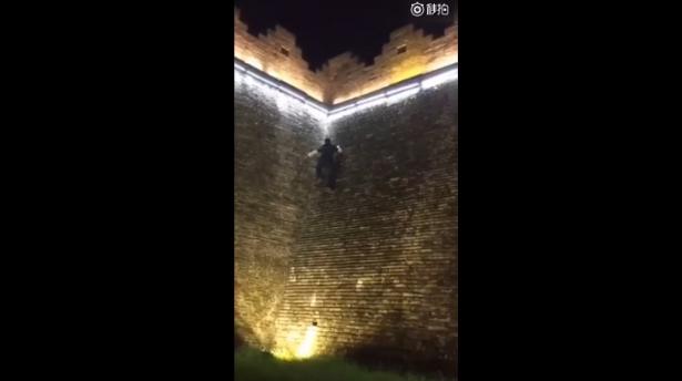 男游客穿黑衣爬景区宋城墙 为博眼球简直了