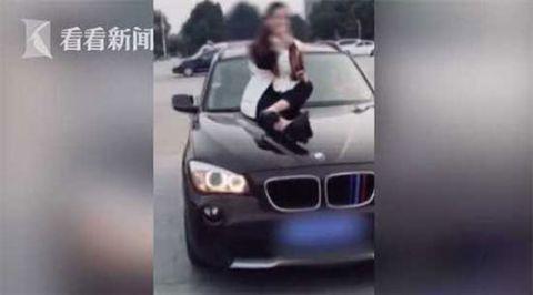 女子坐引擎盖上K歌 此举动已涉嫌违法