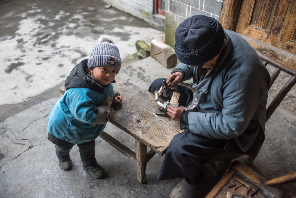 2月28日,龙吉堂錾刻银饰时,曾外孙在一旁观看。