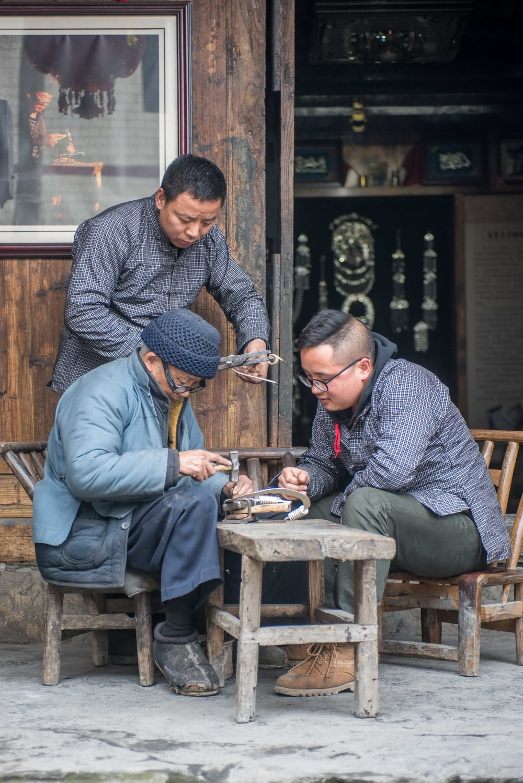 2月28日,龙吉堂(左前)与儿子龙先虎(后)在教龙建平錾刻技艺。